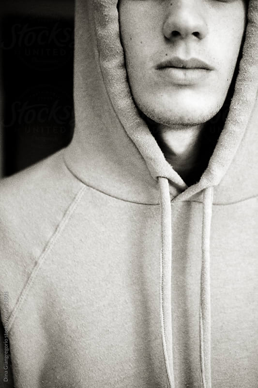 Lower portion of boys face wearing hooded sweatshirt by Dina Giangregorio for Stocksy United