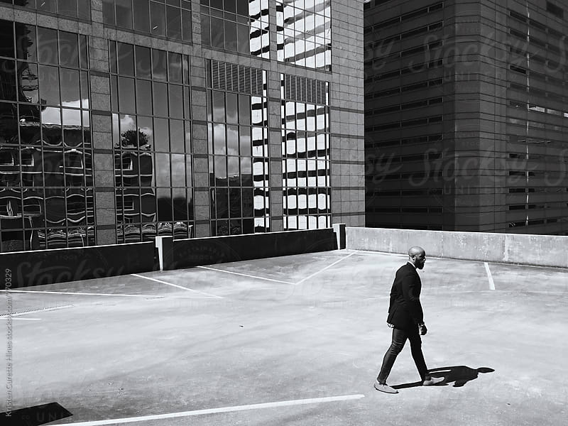 Mobile capture of A business man walking alone on a rooftop outdoor parking garage.  by Kristen Curette Hines for Stocksy United
