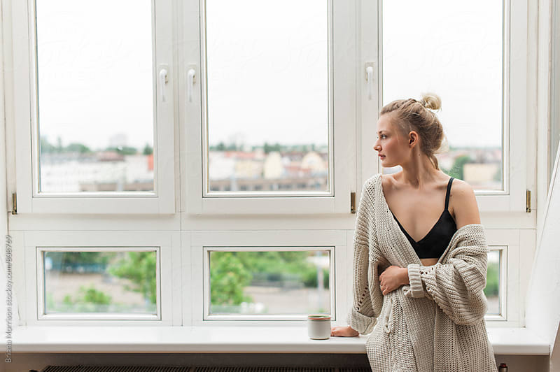 Young Woman in Cozy Pajamas and Sweater Looking out a Window with a Mug of Tea by Briana Morrison for Stocksy United