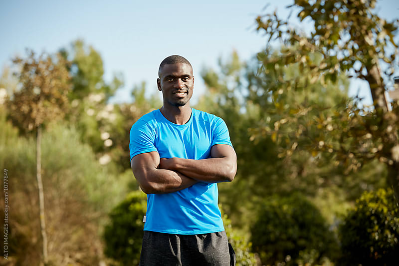 Male Athlete Standing With Arms Crosses In Park by ALTO IMAGES for Stocksy United