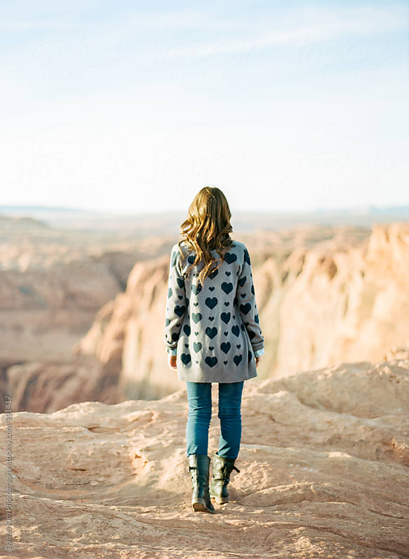young woman overlooking a canyon by Daniel Kim Photography for Stocksy United