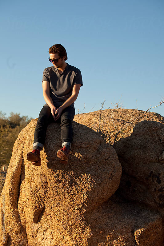 Man Sitting On A Rock In The Desert by Carey Haider for Stocksy United