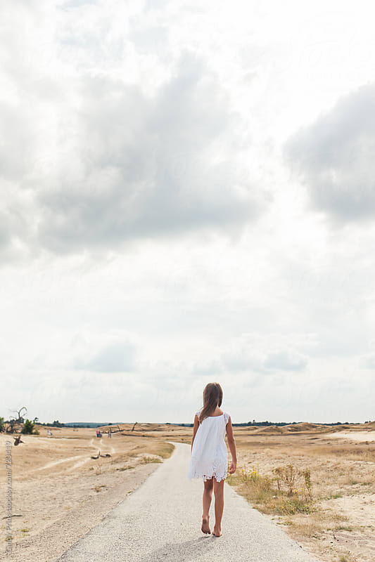 Little girl in a white dress walking on a long road in an open field by Cindy Prins for Stocksy United