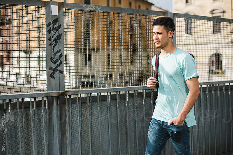 Asian man walking in the city by Simone Becchetti for Stocksy United