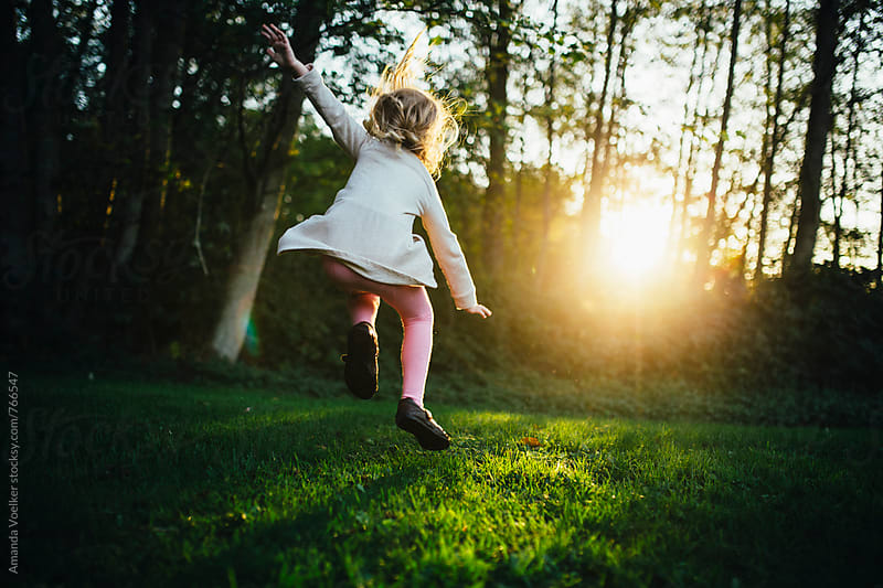 A Little Girl Leaps with Abandon in the light of the setting sun by Amanda Voelker for Stocksy United