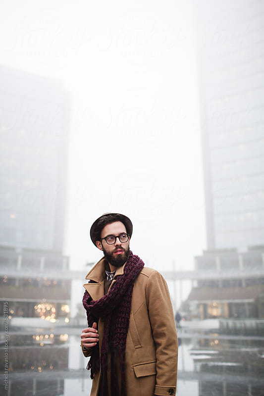 Young man with a beard standing in front of a corporate building by michela ravasio for Stocksy United