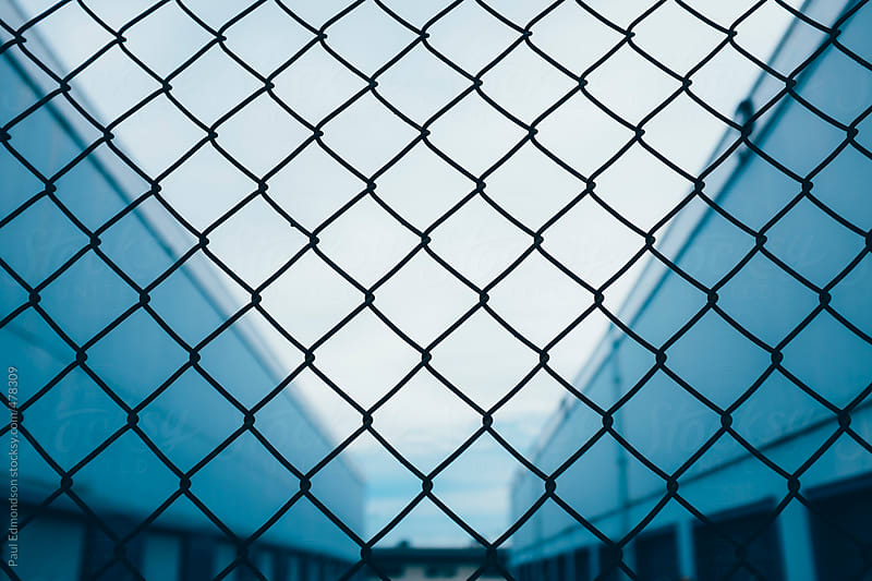 Chain-link fence in front of industrial warehouse by Paul Edmondson for Stocksy United