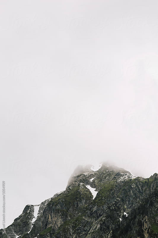 Mountain summit with stormy clouds by Miquel Llonch for Stocksy United