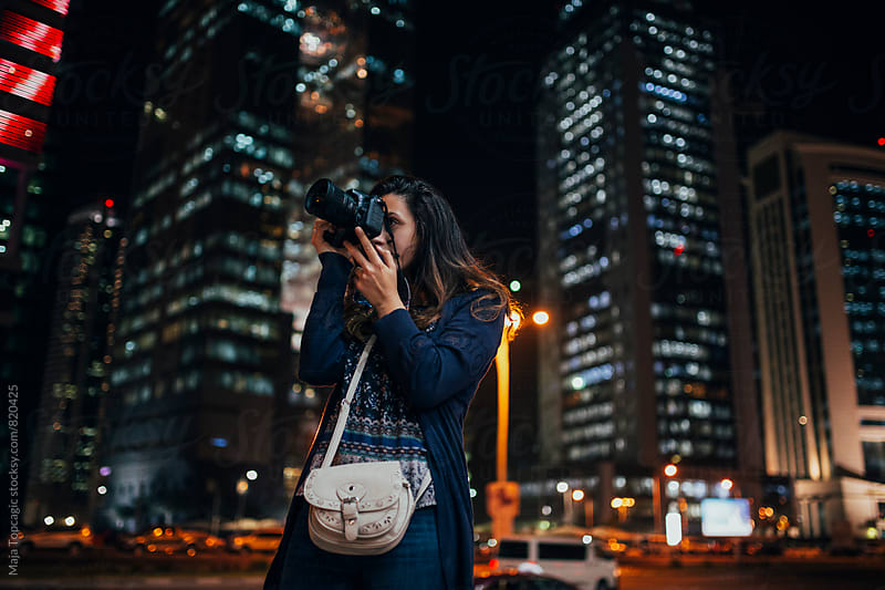 Young woman photographer taking photos  by Maja Topcagic for Stocksy United