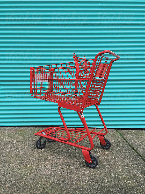 Red grocery cart in front of vibrant metal wall by Paul Edmondson for Stocksy United