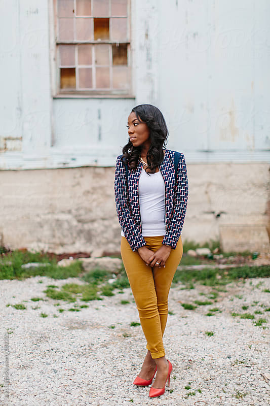 Trendy and fashionable African-American woman standing in front of an abandoned warehouse by Jakob for Stocksy United