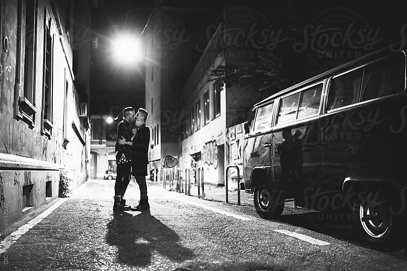 Boyfriends kissing in the street at night by Simone Becchetti for Stocksy United