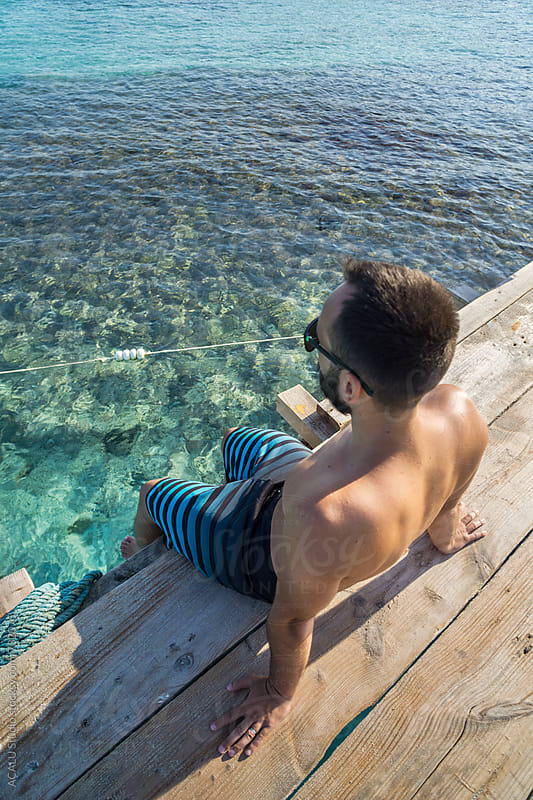 Young man sitting on a jetty with clear water by ACALU Studio for Stocksy United