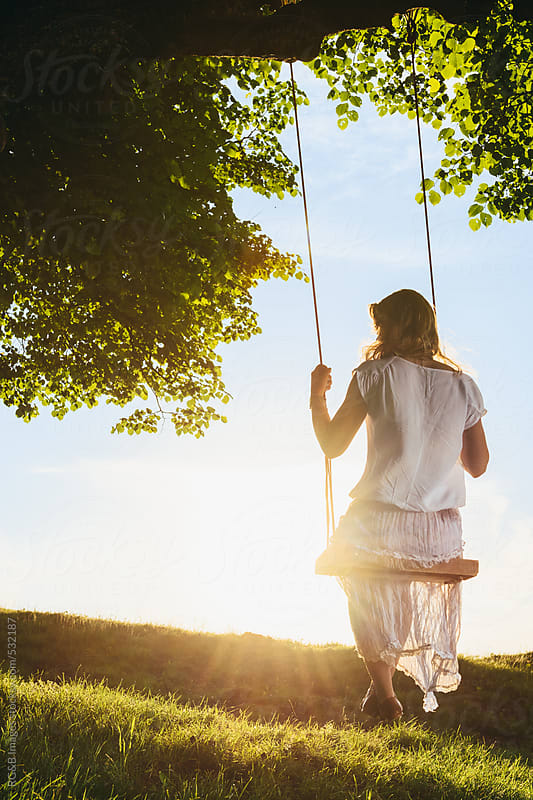 Young woman sitting on a swing in a tree by RG&B Images for Stocksy United