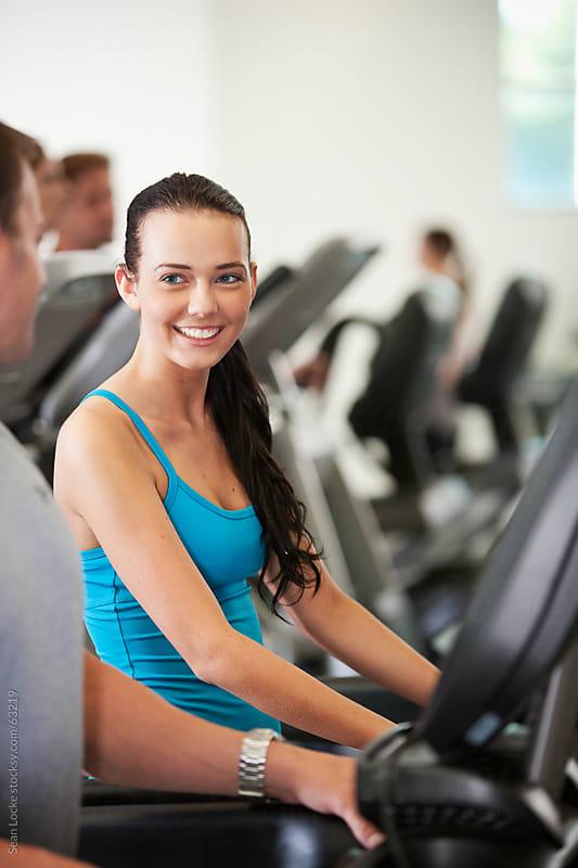 Gym: Woman Flirts with Man While on Treadmill by Sean Locke for Stocksy United
