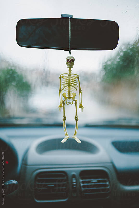 Tiny halloween figure of the skeleton hanging inside of a car  by Sanja (Lydia) Kulusic for Stocksy United