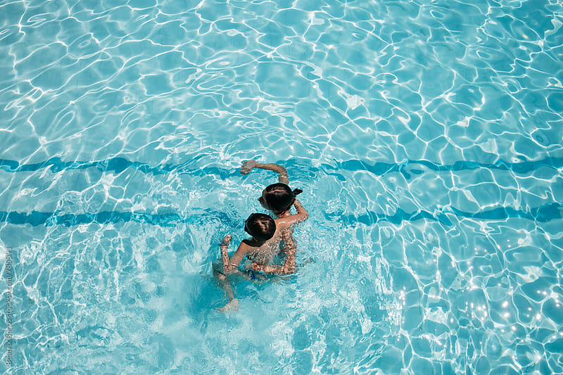 Boy and girl hugging each other in an outdoors swimming pool in the Summer by Beatrix Boros for Stocksy United