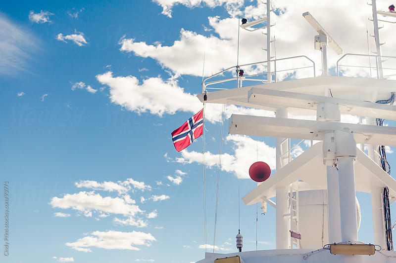 The Norwegian flag on the top of a ship against the blue summer sky by Cindy Prins for Stocksy United