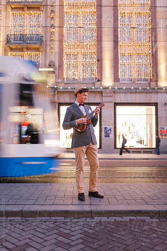 Young man in a classic suit playing a ukelele, in a busy street by Ivo de Bruijn for Stocksy United