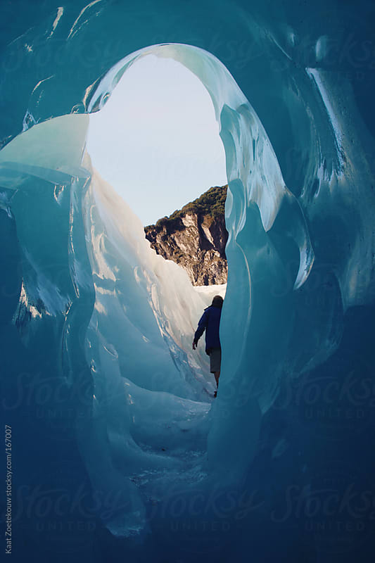 View from a blue colored ice crevice, with a silhouetted man exiting the tunneled structure towards the sunlit wintery landscape.  by Kaat Zoetekouw for Stocksy United