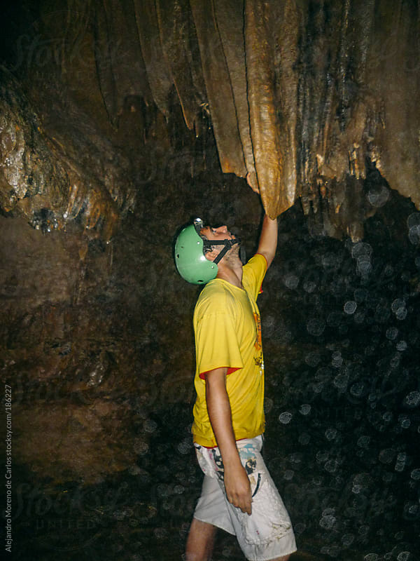 Young adventurer man doing speleology on a cave looking stalactite by Alejandro Moreno de Carlos for Stocksy United