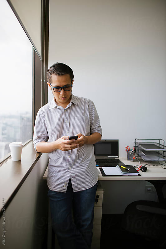 An Asian businessman texting by Alita Ong for Stocksy United