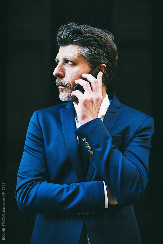 Portrait of a mature businessman talking on phone. by BONNINSTUDIO for Stocksy United