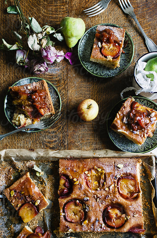 Sticky plumb pudding with apple and pear compote on a rustic wooden table. by Darren Muir for Stocksy United