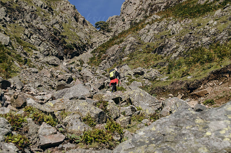 Female hiker scrambling up rocky terrain by Neil Warburton for Stocksy United