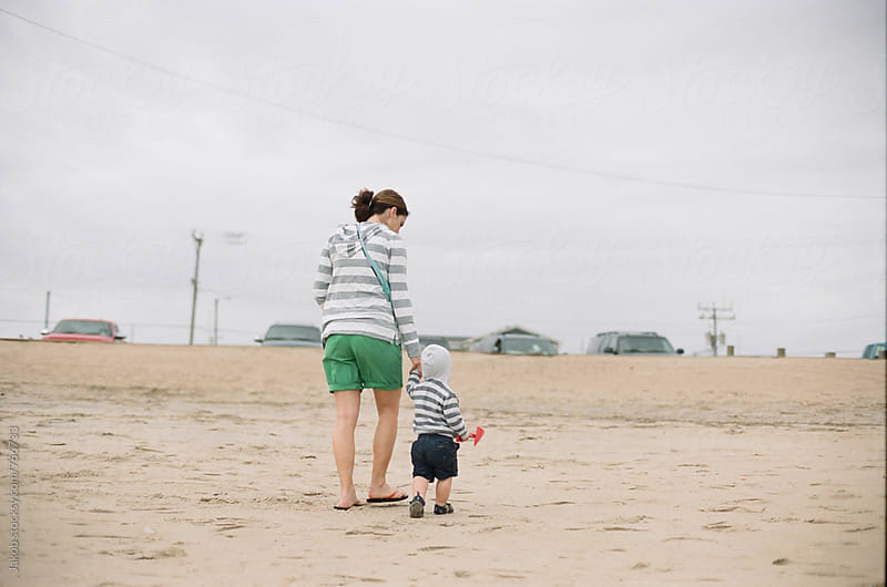 Mother and son holding hands walking home from playing on the beach by Jakob for Stocksy United