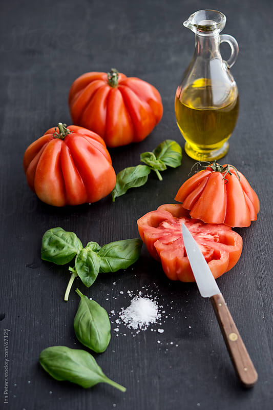 Food: Bulls Heart Tomatos, basil, salt and olive oil by Ina Peters for Stocksy United