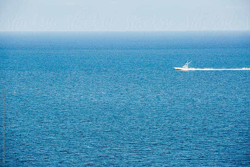 Speedboat sailing through the blue sea in the ocean on a clear day by Alejandro Moreno de Carlos for Stocksy United