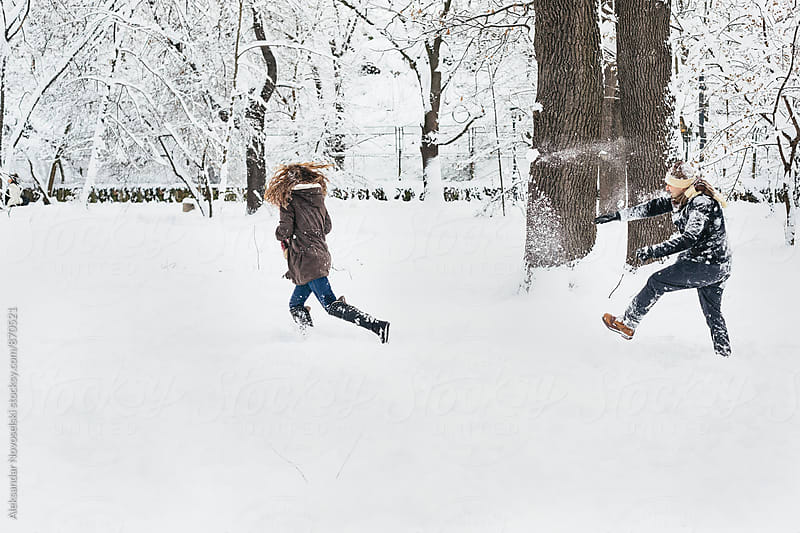 Two friends playing in the snow by Aleksandar Novoselski for Stocksy United