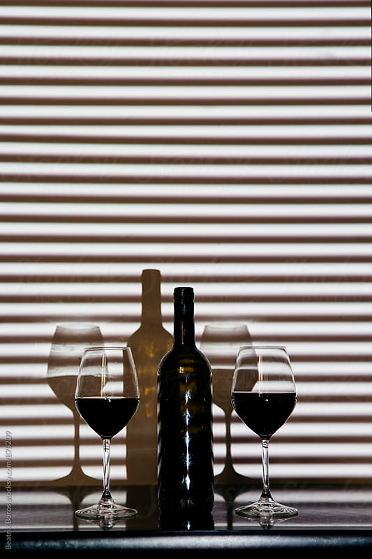 Bottle of wine with two glasses in striped shadow by Beatrix Boros for Stocksy United