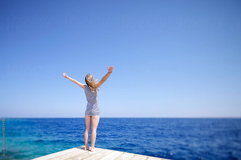 Young woman standinag on pier looking at sea with raised arms. by Ilya for Stocksy United