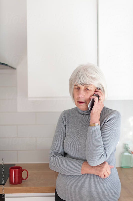 senior woman using talkiing on her mobile phone by Lee Avison for Stocksy United