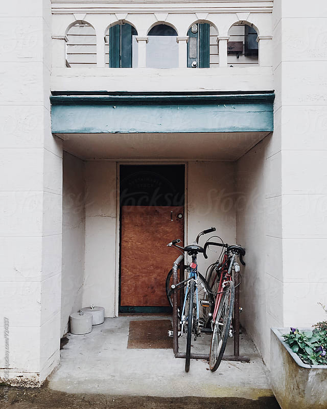 Two bikes leaning against a wall by a brown door by KATIE + JOE for Stocksy United