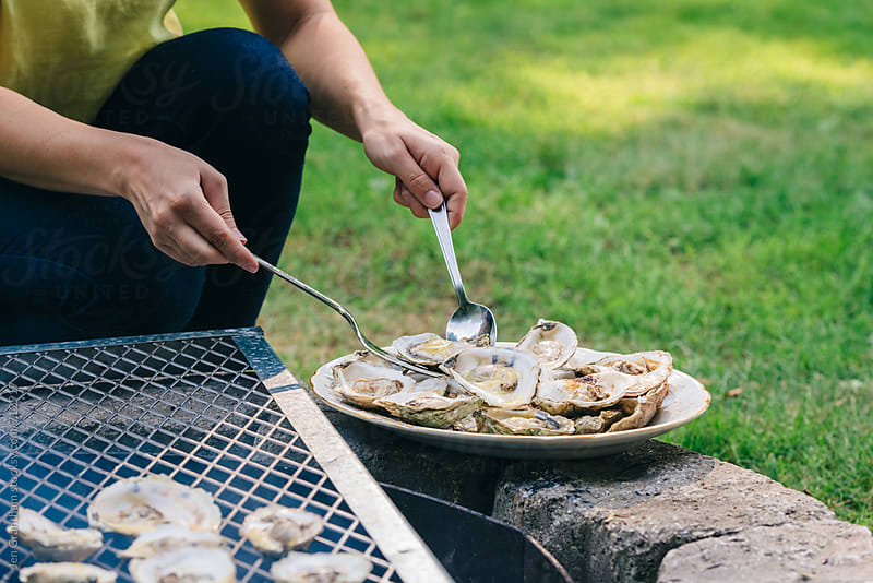 Woman taking cooked oysters off grill by Jen Grantham for Stocksy United