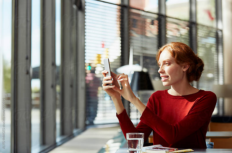 Happy Young Woman Using Mobile Phone In Restaurant by ALTO IMAGES for Stocksy United