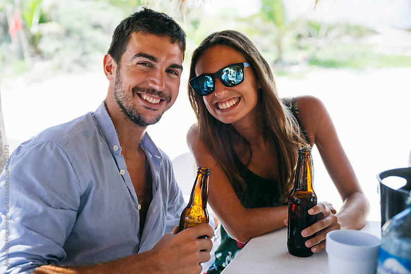 Young happy couple posing for a picture at a beach bar with their drinks by Alejandro Moreno de Carlos for Stocksy United