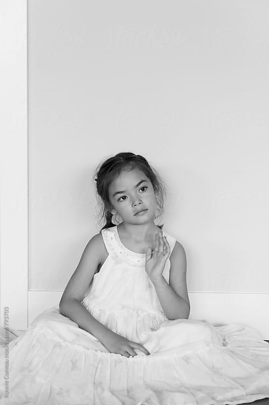 Little Girl In White Dress At Home by Ronnie Comeau for Stocksy United