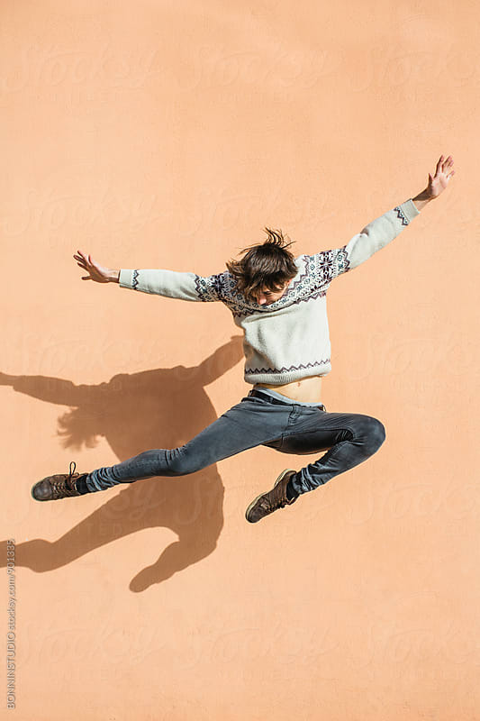 Teenage boy jumping high in front of a wall. by BONNINSTUDIO for Stocksy United