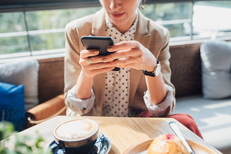 Caucasian Woman Sitting at a Cafe and Texting by Lumina for Stocksy United