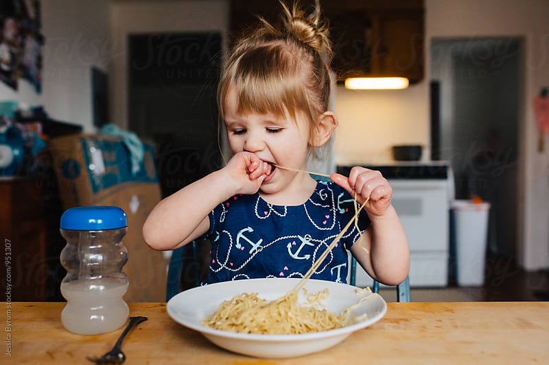 Toddler girl eating noodles by Jessica Byrum for Stocksy United