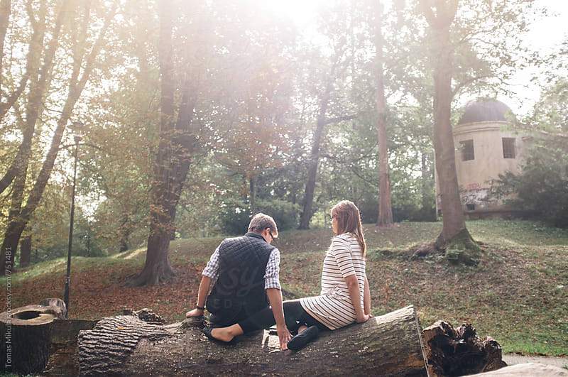 Couple is sitting on the fallen tree by Tomas Mikula for Stocksy United