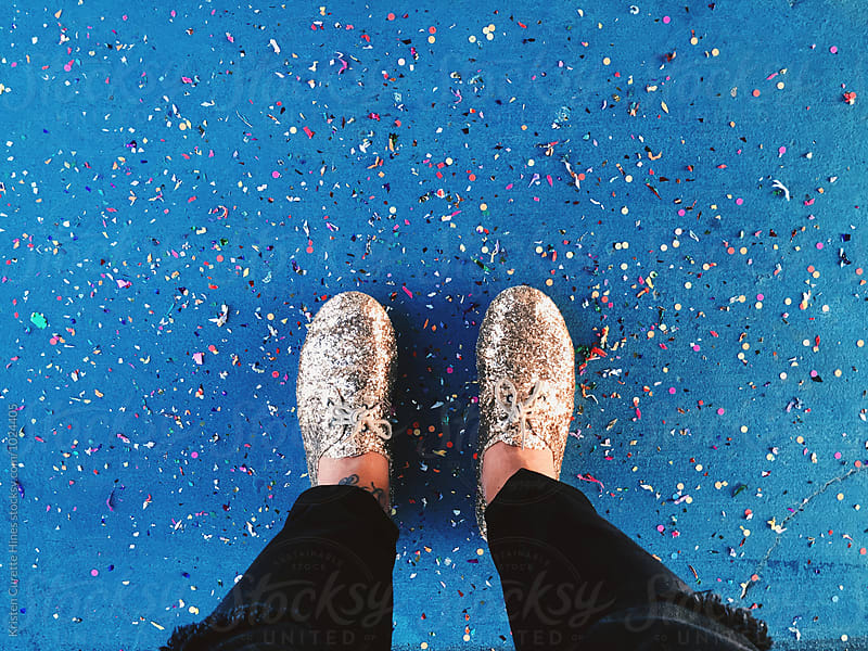 First person view of someone looking down at their shoes and confetti on the ground  by Kristen Curette Hines for Stocksy United