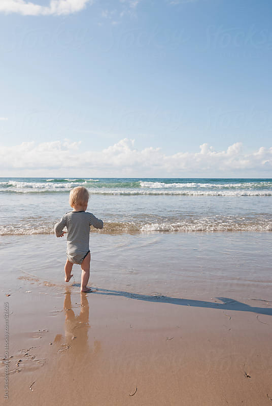 One year old boy running into the ocean by Urs Siedentop & Co for Stocksy United