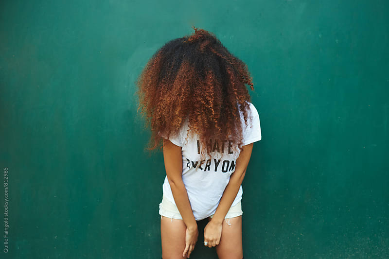 Young Afro-American woman leaning on green background by Guille Faingold for Stocksy United