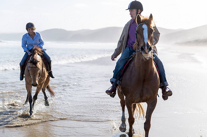 Senior male and female riding horseback and laughing in shorebreak with reflections on wet sand by Ben Ryan for Stocksy United