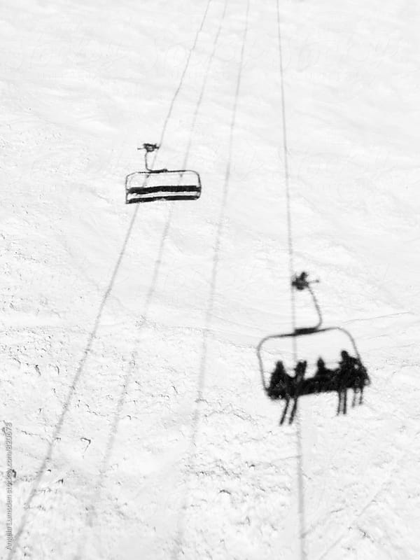 Shadow of three pople riding a chairlift on a groomed ski slope as an empty chair passes by by Angela Lumsden for Stocksy United